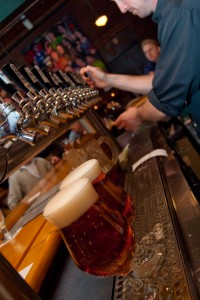 A bartender pours beers from taps.